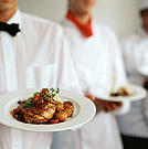 two chefs and a waiter standing in a row